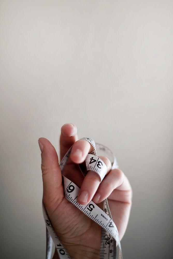 personne avec un metre mesureur enroulé autour de la main